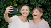 büyükbaba veya büyükanne : Pretty old granny and her granddaughter doing selfie outdoor, fooling around, looking at camera and laughing to smartphone camera. Technology, memory, family concept