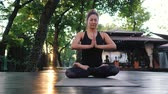 gratidão : Pretty woman with oriental face practicing yoga, namaste gratitude mudra alone in tropical island. Girl in lotus pose. Religion, purity, resignation, spirituality concept. Padmasana. Vídeos