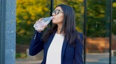 ela : Young businesswoman near office building drinks mineral water from bottle. Beautiful girl in eyeglasses drinking clean water. Healthy lifestyle concept