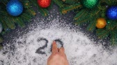 paketlenmiş : Male hands draw numbers of new 2019 year in the snow. Top view. Beautiful holidays background of green spruce branches decorated with christmas balls Stok Video