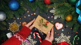 papel de embrulho : Womans hands puts gift wrapped in craft paper on table and then takes it. Black table with Christmas decorations - gingerbread, snowflakes, lollipops.Top plan view. Festive mood Stock Footage