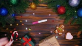 lolipop : Female hands puts positive pregnancy test on table as christmas present. Wooden table with new year decorations. Top plan view. Festive mood, maternity concept.