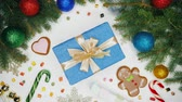 lolipop : Female hands giving present wrapped in blue paper with golden bow and then takes it. Wooden white table with Christmas decorations - gingerbread, snowflakes, lollipops. Stok Video