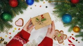 lolipop : Top view. Womans hands puts gift wrapped in craftool paper decorated with sprig of spruce and wild rose berries. Wooden white table decorated with Christmas stuff, garlands, gingerbread, lollipops. Stok Video