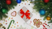 lolipop : Festive composition of gift in Christmas decorations on white surface background. Flat lay, top view. New year holiday frame of fir branches, cookies, lollipop canes, sweets.