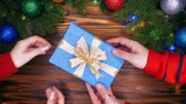 borítás : Couple exchanging Christmas present. Male hands in warm red sweater giving present in blue paper to his girlfriend or wife. Wooden table with new year decorations. Top plan view
