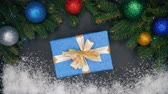 lolipop : Womans hands puts gift wrapped in blue paper in the center of frame made with fir branches and snow and then takes it. Christmas decorations - flashing garland lights, baubles