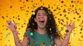 трилистник : Young latin girl with curly hair dancing and having fun in confetti rain on yellow background. Woman celebrating, depicts joy and happiness. Success, victory, holiday concept.