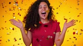Young latin girl with curly hair dancing and having fun in confetti rain on yellow background. Woman celebrating, depicts joy and happiness. Success, victory, holiday concept.