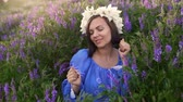 аромат : Pretty woman with flower wreath dancing in purple field. Girl in blue having fun
