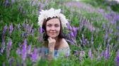аромат : Beautiful woman with white flower wreath in violet field. Girl in blue dress smiling.