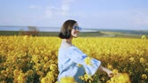 рапсовое : Young woman in dress rejoices, spinning around in rapeseed yellow flowers field. Freedom, love, nature concept.