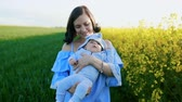 řepkový : Portrait of young mother with newborn son having fun in yellow field. Love, family, joy concept.