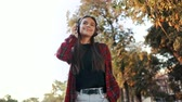 atitude : Portrait of attractive girl dancing with earphones in park. Woman smiling. moves to the rhythm.Friendly appearance of modern trendy hipster Vídeos