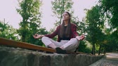 meditando : Young calm student girl relaxing, meditating at green park. Woman calms down, breathes deeply. Yoga, zen, health lifestyle concept. Archivo de Video