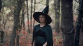 vampiro : Woman as black witch walks between trees in autumn forest.Girl in long dress, cape, fairy hat. Halloween concept, cosplay dressing up Filmati Stock