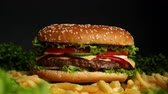 Juicy beef burger with cutlet, onion, vegetables, melted cheese, lettuce, sauce and topped sesame seeds. Isolated hamburger rotates on dark background, close-up view