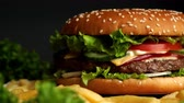 Big appetizing burger with meat cutlet, onion, vegetables, melted cheese, lettuce and mayonnaise sauce. Isolated hamburger rotates on dark smoke background, close-up view