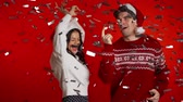 cardigã : Excited couple Santa Claus hats dancing, applauding, having fun, rejoices over confetti rain in red studio. Concept of Christmas, New Year, happiness, party, winning.
