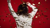 luz frontal : Excited african american woman dancing, having fun, rejoices over confetti rain in red studio. Concept of Christmas, New Year, happiness, party, winning Archivo de Video