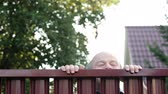 neighbor : Senior man looking through fence spying on his neighbor. Curious pensioner want to see what is going on outdoor. Looped video Stock Footage