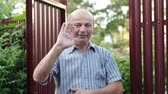 říci : Friendly caucasian old man waving hi or farewell, isolated outdoors background with green trees and fence. Homeowmer saying goodbye to his guest