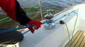 Yachtsman in red gloves sheets with windlass. 4K