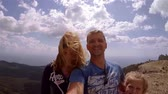 Dad and two daughters make selfie video from top of mountain. Everyone smiles and peeps.