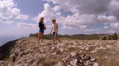 Two girls stand on the edge of mountain.The lilttle one make photos of the elder. The elder one wipe camer with t-shirt. Stock Footage