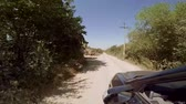 missão : Driving along foothill country road past green trees and cottages . Camera is in steadycam. HD Vídeos