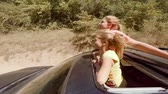 vysedět : Two happy young blondes laughing leaping out of hatch of the car on the move against the forest
