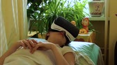 febre : Sad sick caucasian girl lies in hospital on bed under a blanket in VR glasses.