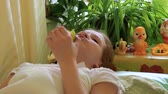 cot : Girl eats apple lying on bed. Stock Footage