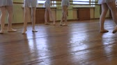 тапочка : Girls in ballet shoes do exercises during ballet class in frayed classroom