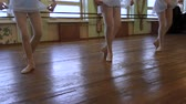 sukénka : Legs of girls doing exrcises during ballet lesson in frayed classroom.
