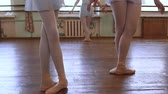 frayed : Girls stand in third position and begin to dance in ballet classroom.
