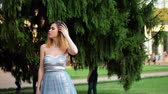 excitação : Beautiful skinny girl in dress poses on background of fir tree, then approaches to camera during photo session in antique estate. Stock Footage