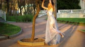 luxúria : Beautiful skinny girl in silver and blue dress poses holding on tree, raising leg, adjusting dress during photo session in antique estate. Vídeos