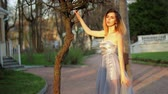 excitação : Beautiful skinny girl in silver and blue dress poses holding on tree, raising leg, adjusting dress during photo session in antique estate. Stock Footage