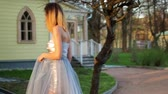 excitação : Beautiful skinny girl in silver and blue dress holds on tree, goes upstairs getting ready to pose during photo session in antique estate. Stock Footage