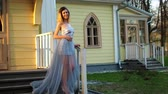 excitação : Beautiful skinny girl in silver and blue dress and in high heeled shoes poses standing on stairs of wooden house during photo session in antique estate.