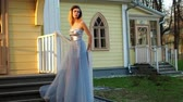 excitação : Beautiful skinny upset girl in silver and blue dress and in high heeled shoes poses standing on stairs of wooden house during photo session in antique estate.