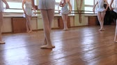 tutu skirt : Girls in blue ballet suits stand in third position and begin dancing in circle on floor of frayed ballet classroom. HD Stock Footage