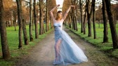 excitação : Attractive girl with black brows and curly hair in silver and blue dress adjusts her dress and poses standing on path of parkway during photoshoot.