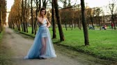excitação : Attractive girl with black brows and curly hair in silver and blue dress poses standing on path of parkway and walks staright ahead during photoshoot.