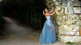 excitação : Attractive girl with black brows and curly hair in silver and blue dress poses near stony wall of arc during photoshoot. Stock Footage