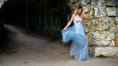 excitação : Skinny girl in silver and blue dress in high heeled shoes stands near stony wall of arc and dances as gipsy preparing to pose during photo shoot in antique estate. Stock Footage