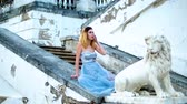 excitação : Attractive girl with black brows and curly hair in silver and blue dress sits on stone balustrade near lion statue during photoshoot in antique estate.