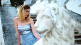 excitação : Attractive girl with black brows and curly hair in silver and blue dress sits on stone balustrade near lion statue and poses during photoshoot in antique estate. Stock Footage