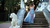 excitação : Attractive girl in silver and blue dress in high heeled shoes goes up stairs with stone balustrade near lion statue and gets ready to pose during photoshoot in antique estate. Stock Footage